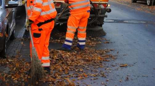 Straßenreinigung fegt im Herbst Laubblätter mit Kehrmaschine